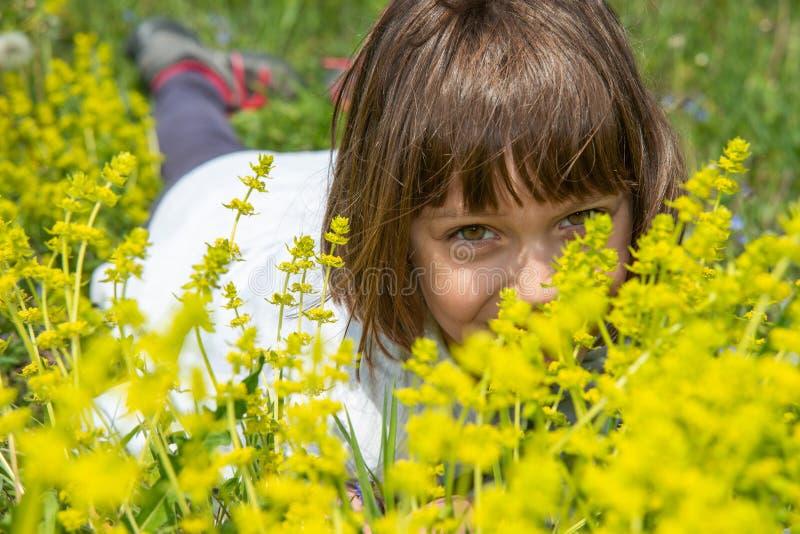 Χαριτωμένο μικρό κορίτσι που βρίσκεται στη χλόη και τα λουλούδια και το γέλιο στοκ εικόνα