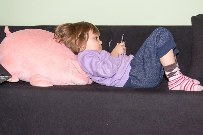 Χαριτωμένο μικρό κορίτσι που βρίσκεται στο κρεβάτι με το γεμισμένο χοίρο παιχνιδιών και το κινητό τηλέφωνό της στοκ φωτογραφία