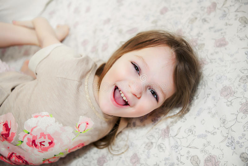 Χαριτωμένο μικρό κορίτσι που γελά στο κρεβάτι στοκ εικόνα