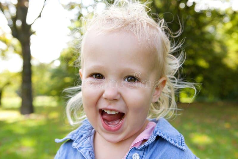 Χαριτωμένο μικρό κορίτσι που γελά υπαίθρια στοκ φωτογραφία με δικαίωμα ελεύθερης χρήσης