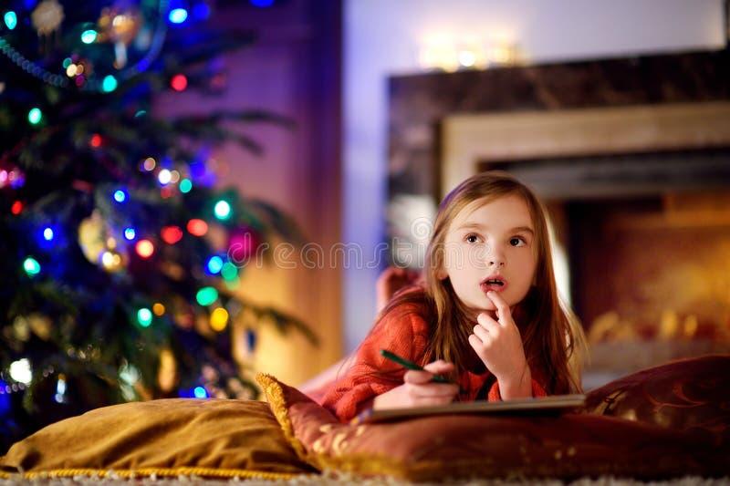 Χαριτωμένο μικρό κορίτσι που γράφει μια επιστολή σε Santa από μια εστία στα Χριστούγεννα στοκ φωτογραφία με δικαίωμα ελεύθερης χρήσης