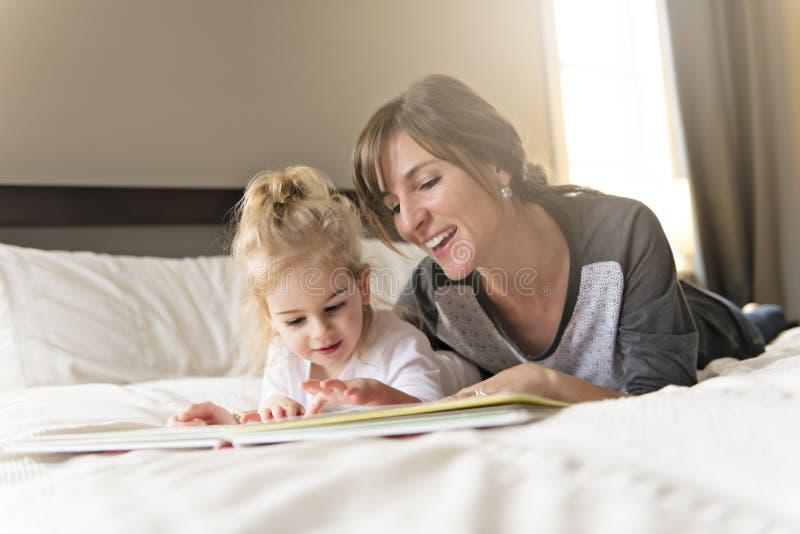 Χαριτωμένο μικρό κορίτσι που διαβάζει ένα βιβλίο με τη μητέρα της στην κρεβατοκάμαρα στοκ εικόνες με δικαίωμα ελεύθερης χρήσης