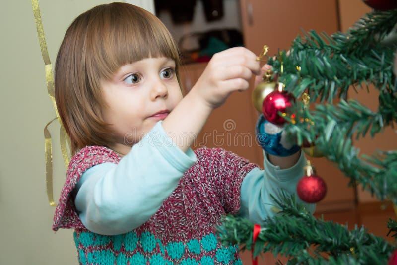 Χαριτωμένο μικρό κορίτσι που διακοσμεί το χριστουγεννιάτικο δέντρο στοκ εικόνες