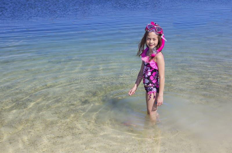 Χαριτωμένο μικρό κορίτσι που κολυμπά με αναπνευτήρα στον ωκεανό στοκ εικόνα