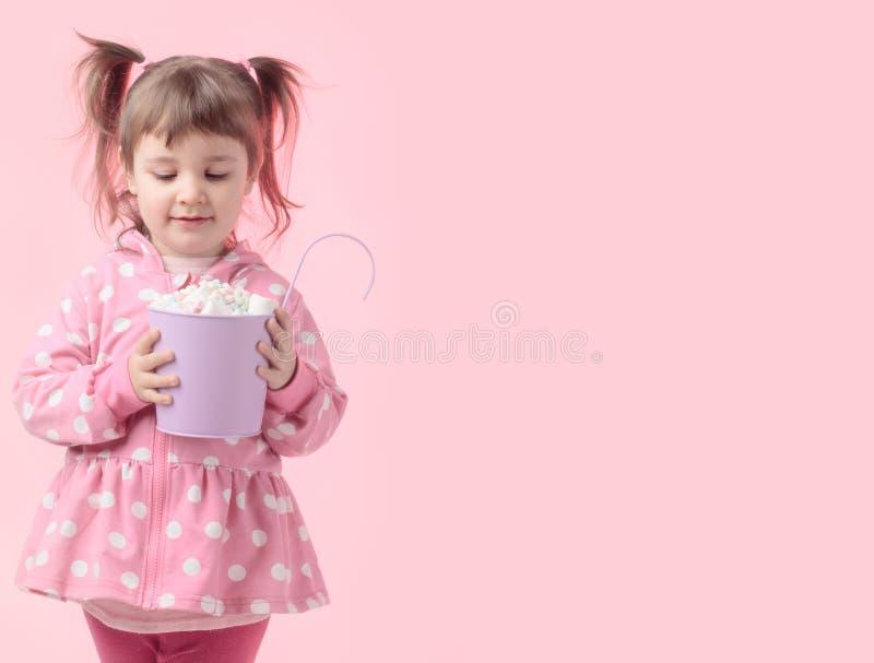 Χαριτωμένο μικρό κορίτσι που κρατά το μικρό ιώδη κάδο marshmallow στοκ φωτογραφίες με δικαίωμα ελεύθερης χρήσης
