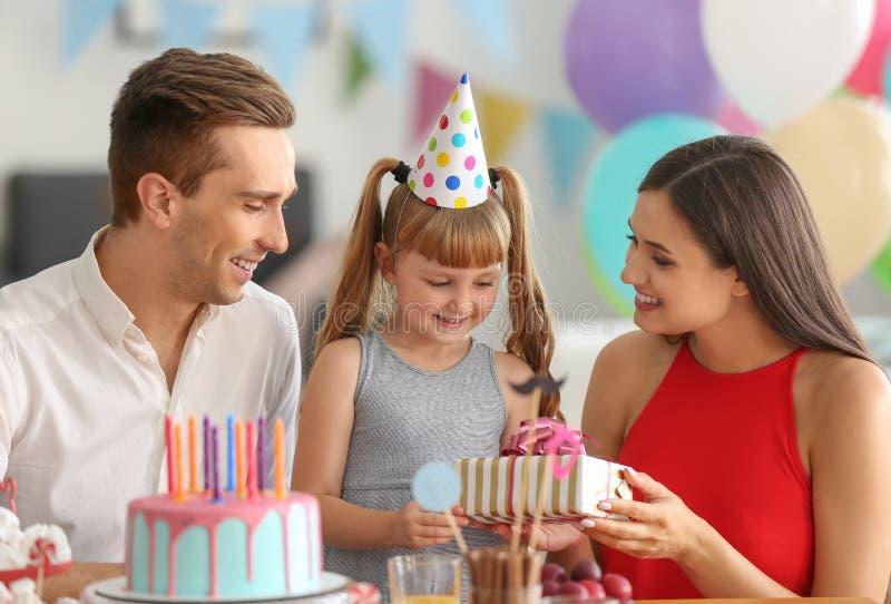 Χαριτωμένο μικρό κορίτσι που λαμβάνει το δώρο γενεθλίων από τους γονείς στο κόμμα στοκ φωτογραφίες με δικαίωμα ελεύθερης χρήσης