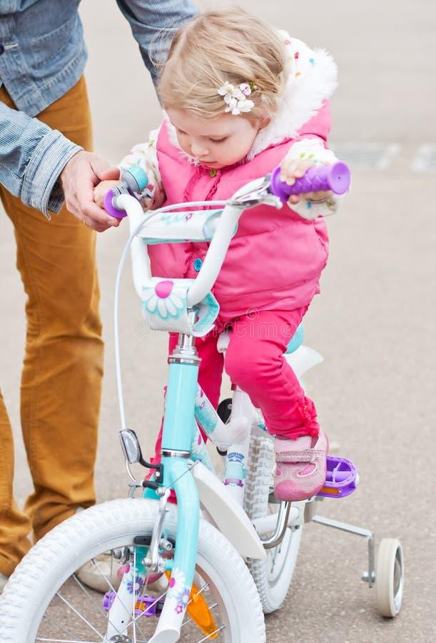 Χαριτωμένο μικρό κορίτσι που μαθαίνει να οδηγά ένα ποδήλατο στοκ φωτογραφία με δικαίωμα ελεύθερης χρήσης