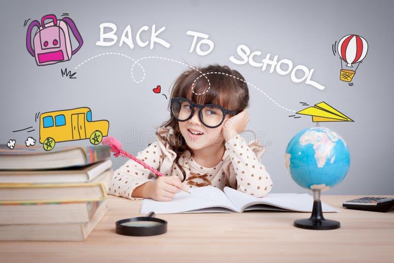Χαριτωμένο μικρό κορίτσι που μελετά στη βιβλιοθήκη και που σκέφτεται, σχολική έννοια στοκ φωτογραφίες