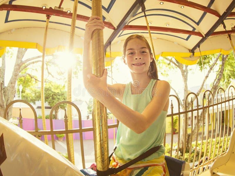 Χαριτωμένο μικρό κορίτσι που οδηγά σε ένα ιπποδρόμιο καρναβαλιού στοκ εικόνες