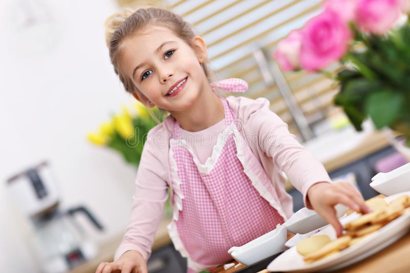 Χαριτωμένο μικρό κορίτσι που προετοιμάζει τα μπισκότα στην κουζίνα στοκ φωτογραφία με δικαίωμα ελεύθερης χρήσης