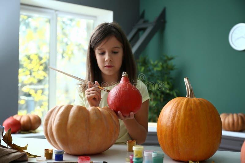 Χαριτωμένο μικρό κορίτσι που προετοιμάζει την κολοκύθα για αποκριές στο σπίτι στοκ εικόνα