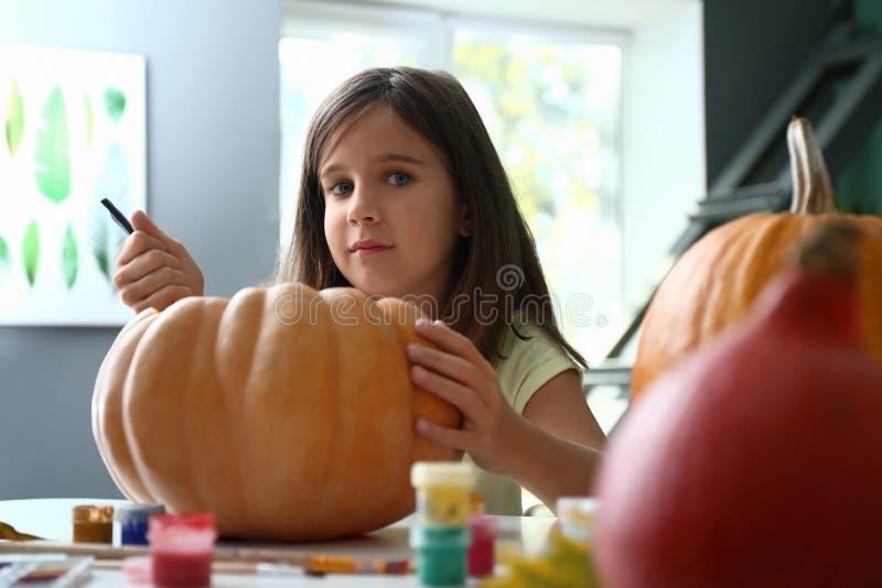 Χαριτωμένο μικρό κορίτσι που προετοιμάζει την κολοκύθα για αποκριές στο σπίτι στοκ εικόνα με δικαίωμα ελεύθερης χρήσης