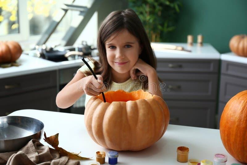 Χαριτωμένο μικρό κορίτσι που προετοιμάζει την κολοκύθα για αποκριές στο σπίτι στοκ φωτογραφία
