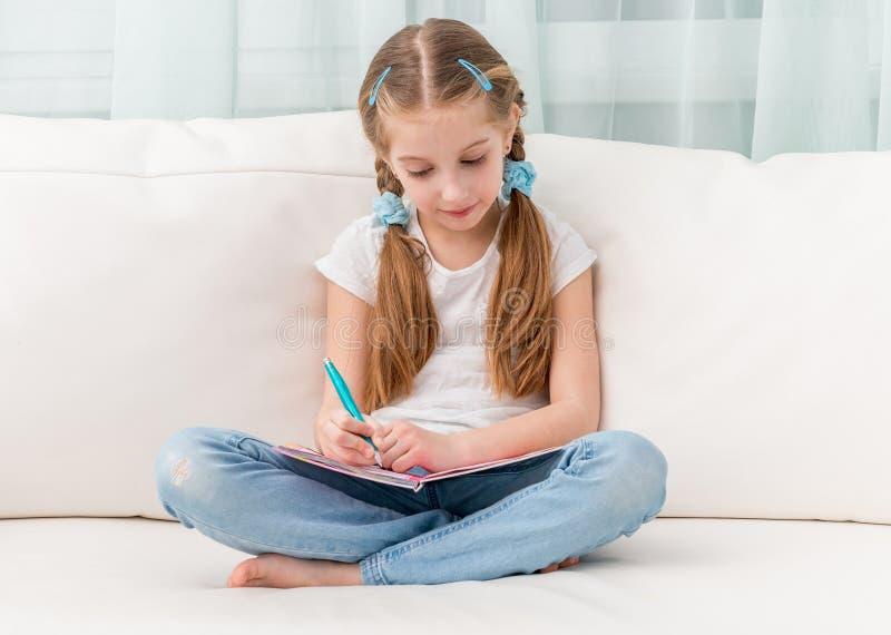 Χαριτωμένο μικρό κορίτσι που συμπληρώνει ένα λεύκωμα φίλων στοκ φωτογραφίες με δικαίωμα ελεύθερης χρήσης