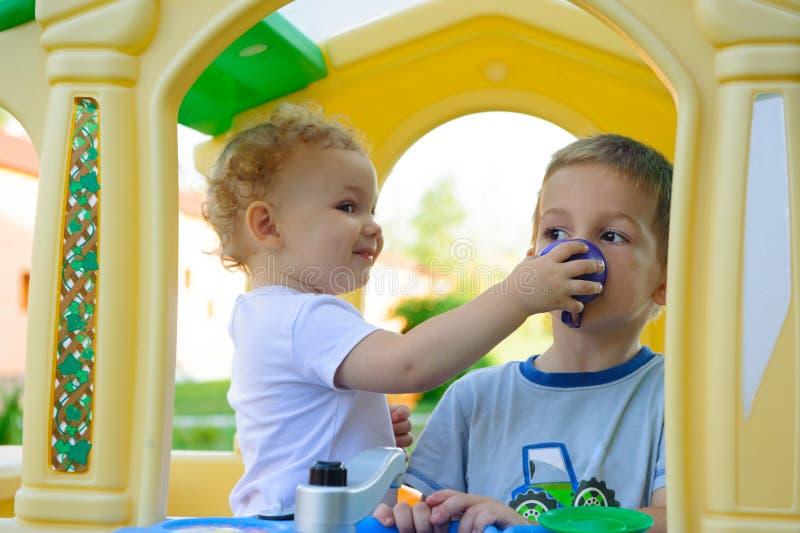 Χαριτωμένο μικρό κορίτσι που ταΐζει τον αδελφό του στοκ εικόνες