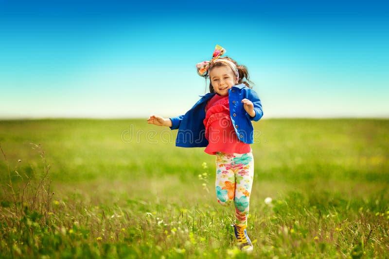 Χαριτωμένο μικρό κορίτσι που τρέχει στο λιβάδι σε έναν τομέα στοκ εικόνες