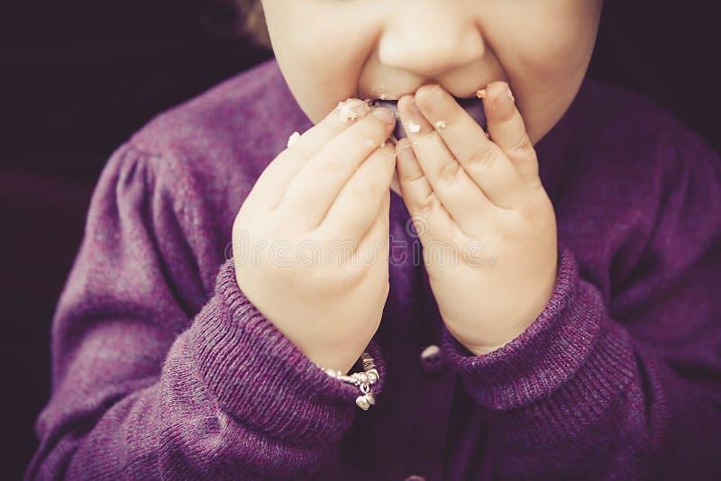 Χαριτωμένο μικρό κορίτσι που τρώει τα γλυκά macarons με το βρώμικο δάχτυλο στοκ φωτογραφία