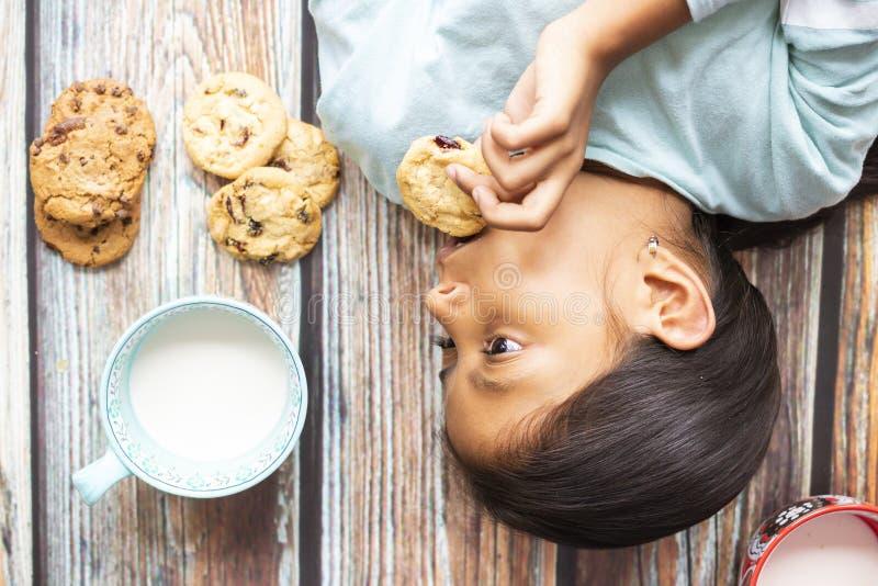 Χαριτωμένο μικρό κορίτσι που τρώει τα μπισκότα με το γάλα στοκ εικόνες
