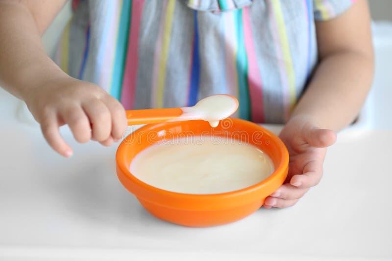 Χαριτωμένο μικρό κορίτσι που τρώει το γιαούρτι στο σπίτι στοκ εικόνα