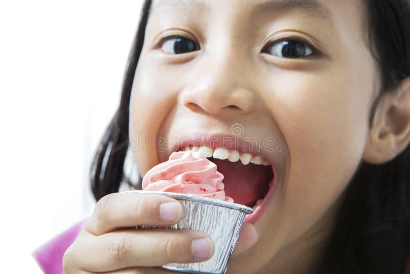 Χαριτωμένο μικρό κορίτσι που τρώει το εύγευστο cupcake στοκ εικόνες με δικαίωμα ελεύθερης χρήσης
