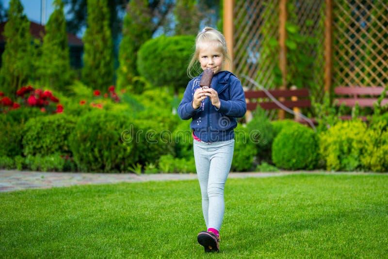 Χαριτωμένο μικρό κορίτσι που τρώει το παγωτό σε έναν κήπο στοκ εικόνες με δικαίωμα ελεύθερης χρήσης