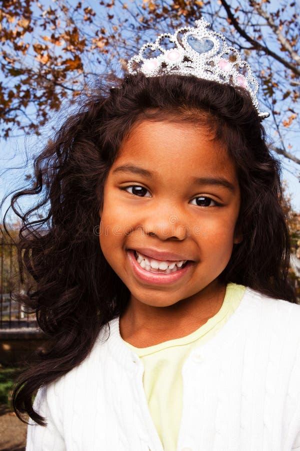 Χαριτωμένο μικρό κορίτσι που χαμογελά φορώντας μια τιάρα στοκ εικόνα