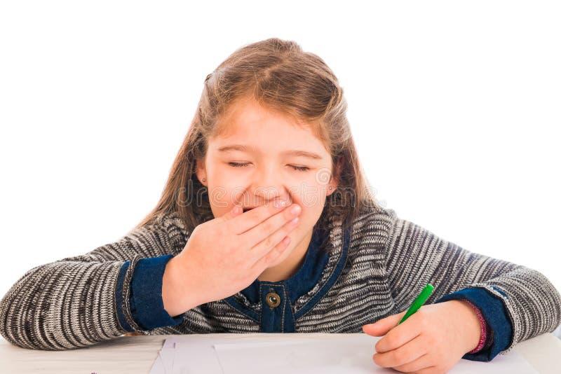 Χαριτωμένο μικρό κορίτσι που χασμουριέται γράφοντας στοκ εικόνες