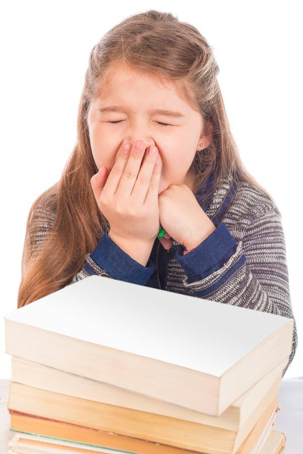 Χαριτωμένο μικρό κορίτσι που χασμουριέται μπροστά από τα βιβλία στοκ εικόνες