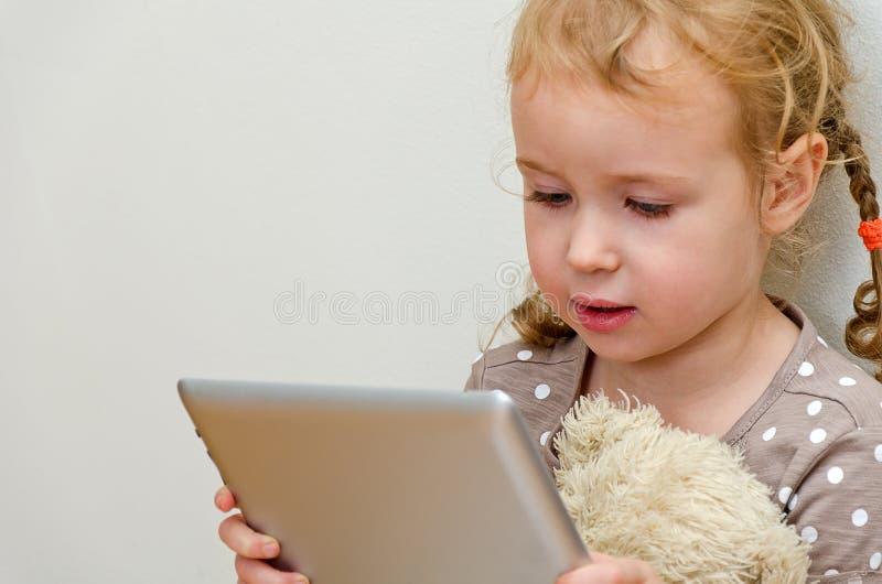 Χαριτωμένο μικρό κορίτσι που χρησιμοποιεί τον υπολογιστή ταμπλετών στοκ εικόνες