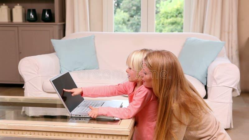 Χαριτωμένο μικρό κορίτσι που χρησιμοποιεί το lap-top με τη μητέρα απόθεμα βίντεο