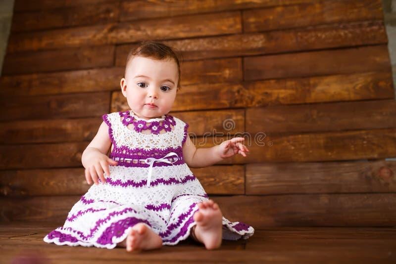 Χαριτωμένο μικρό κορίτσι σε ένα ξύλινο υπόβαθρο στοκ εικόνα
