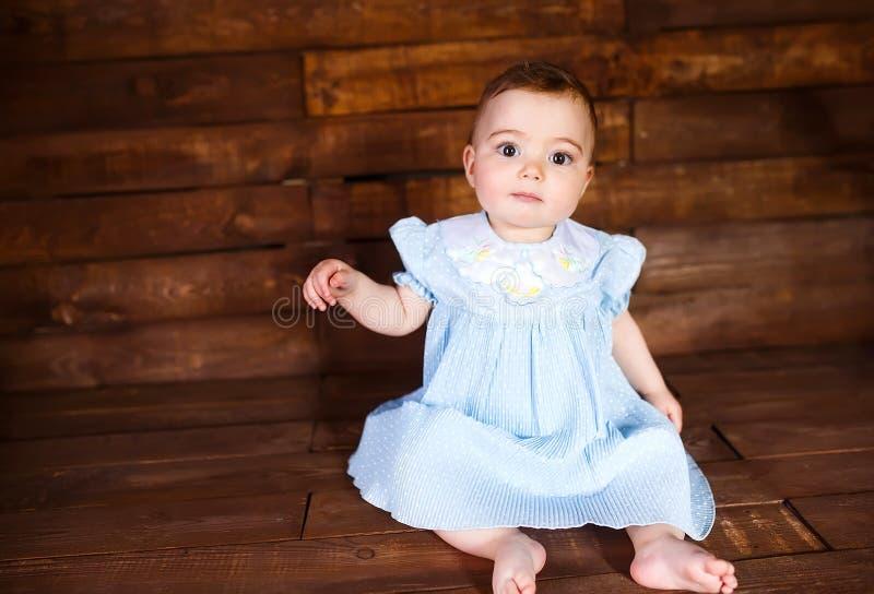 Χαριτωμένο μικρό κορίτσι σε ένα ξύλινο υπόβαθρο στοκ φωτογραφία