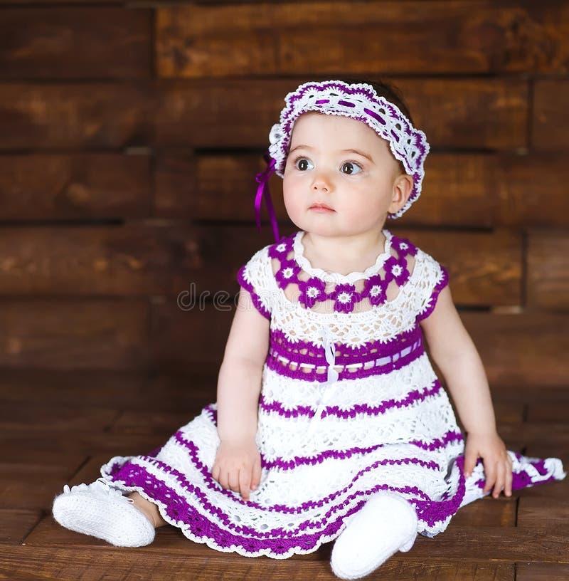 Χαριτωμένο μικρό κορίτσι σε ένα ξύλινο υπόβαθρο στοκ φωτογραφίες με δικαίωμα ελεύθερης χρήσης