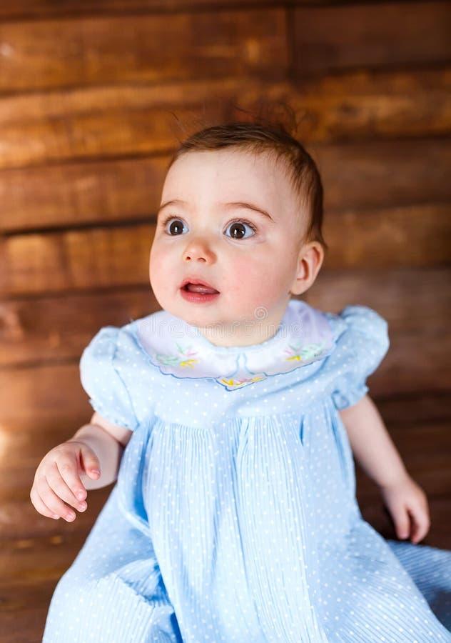 Χαριτωμένο μικρό κορίτσι σε ένα ξύλινο υπόβαθρο στοκ φωτογραφίες