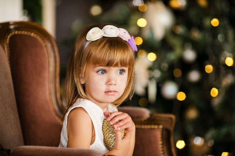 Χαριτωμένο μικρό κορίτσι στο άσπρο φόρεμα με το συμπαθητικό στεφάνι κοντά στο χριστουγεννιάτικο δέντρο στοκ φωτογραφία με δικαίωμα ελεύθερης χρήσης