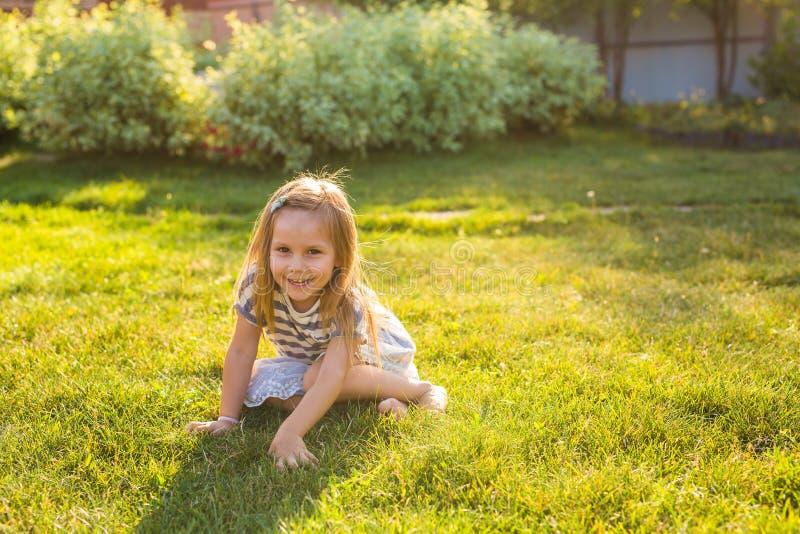 Χαριτωμένο μικρό κορίτσι στο λιβάδι την άνοιξη ή τη θερινή ημέρα στοκ φωτογραφία