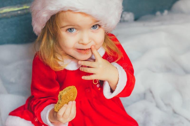 Χαριτωμένο μικρό κορίτσι στο καπέλο Santa με τα μπισκότα στο σπίτι στοκ εικόνες με δικαίωμα ελεύθερης χρήσης