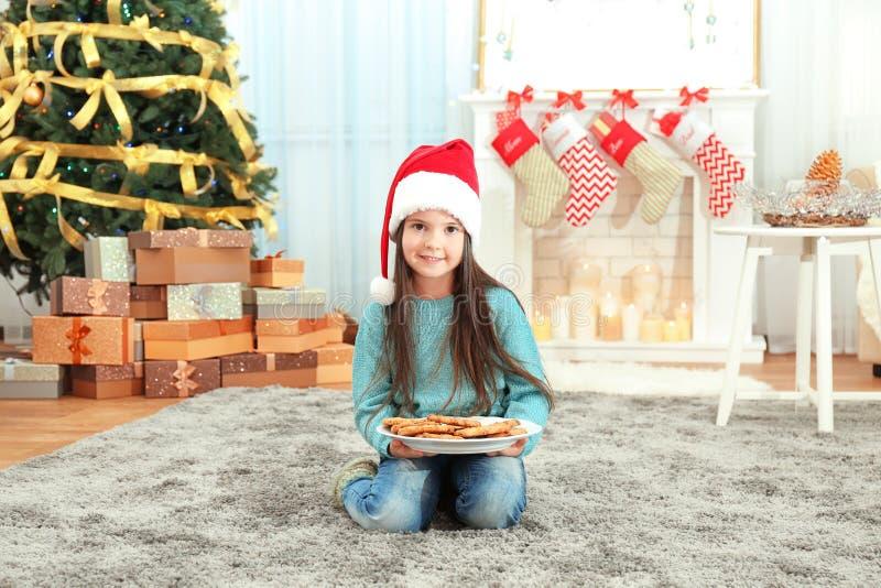 Χαριτωμένο μικρό κορίτσι στο καπέλο Santa με το πιάτο των εύγευστων μπισκότων στο σπίτι στοκ εικόνες