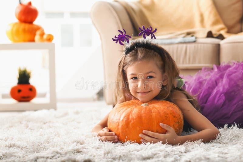 Χαριτωμένο μικρό κορίτσι στο κοστούμι αποκριών και με την κολοκύθα στο σπίτι στοκ εικόνες