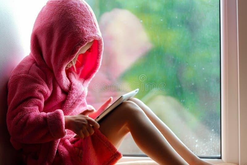 Χαριτωμένο μικρό κορίτσι στο ρόδινο μπουρνούζι που χρησιμοποιεί το PC ταμπλετών καθμένος στη στρωματοειδή φλέβα παραθύρων στοκ φωτογραφία με δικαίωμα ελεύθερης χρήσης