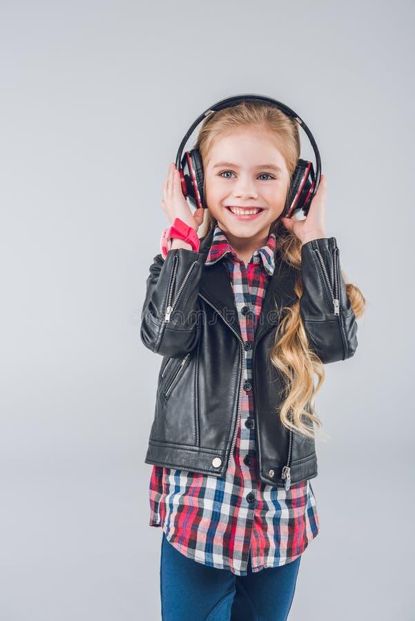 Χαριτωμένο μικρό κορίτσι στο σακάκι δέρματος που φορά τα ακουστικά στοκ εικόνες