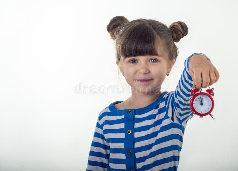 Χαριτωμένο μικρό κορίτσι στο φόρεμα με το κόκκινο ξυπνητήρι στο άσπρο υπόβαθρο στοκ φωτογραφία με δικαίωμα ελεύθερης χρήσης