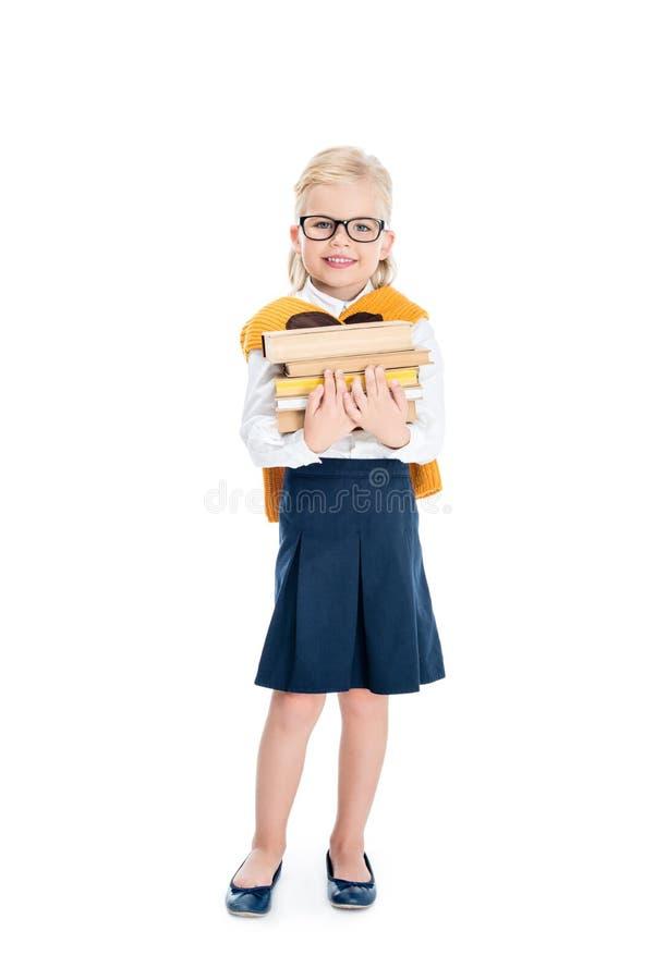χαριτωμένο μικρό κορίτσι eyeglasses που κρατούν το σωρό των βιβλίων και που χαμογελούν στη κάμερα στοκ φωτογραφία με δικαίωμα ελεύθερης χρήσης