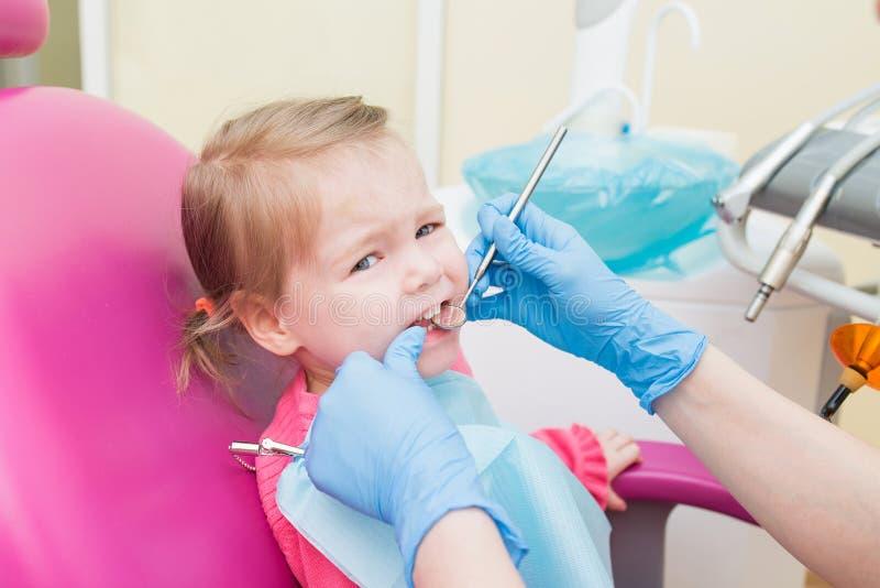 Χαριτωμένο μικρό κορίτσι sitts στην οδοντική καρέκλα στο γραφείο οδοντιάτρων, πορτρέτο κινηματογραφήσεων σε πρώτο πλάνο στοκ εικόνα