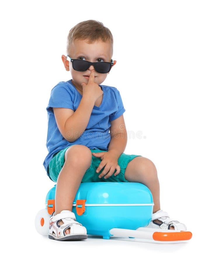 Χαριτωμένο μικρό παιδί με τα γυαλιά ηλίου και την μπλε βαλίτσα στοκ εικόνα με δικαίωμα ελεύθερης χρήσης