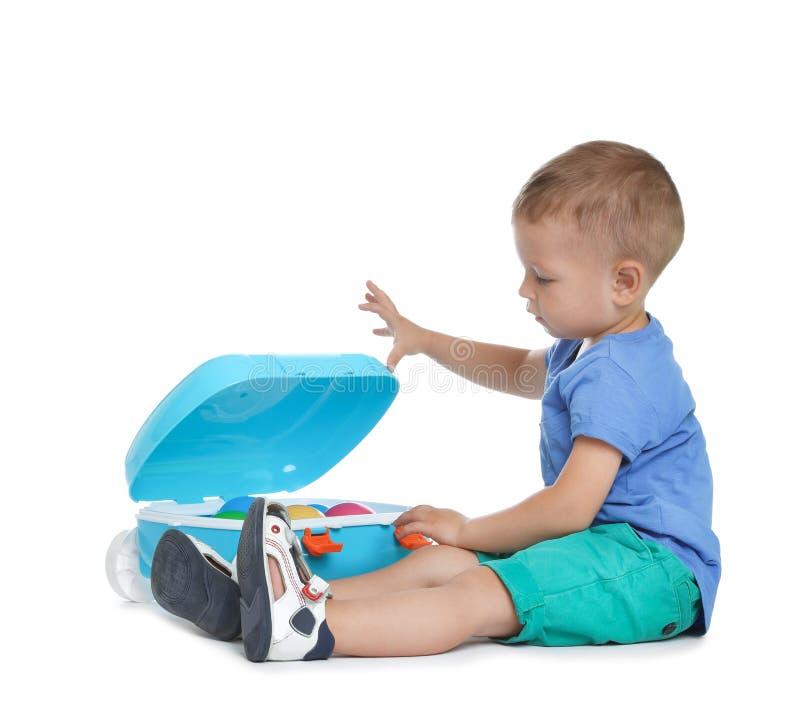 Χαριτωμένο μικρό παιδί με τα παιχνίδια και μπλε βαλίτσα στο λευκό στοκ εικόνες