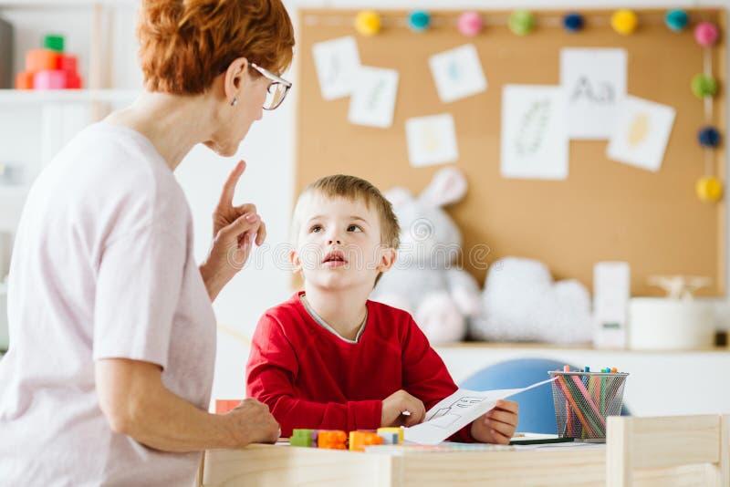 Χαριτωμένο μικρό παιδί με τα προβλήματα κατά τη διάρκεια της συνεδρίασης με το θεράποντα στοκ εικόνα