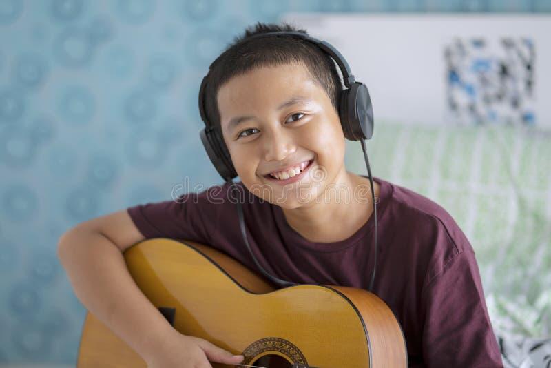 Χαριτωμένο μικρό παιδί με την κάσκα και την κιθάρα στοκ εικόνες