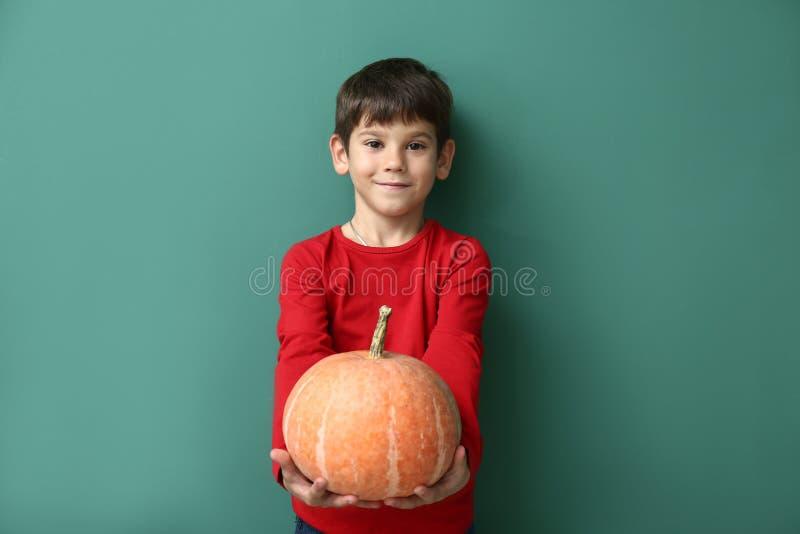 Χαριτωμένο μικρό παιδί με την κολοκύθα στο υπόβαθρο χρώματος στοκ φωτογραφία