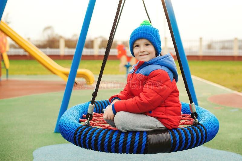 Χαριτωμένο μικρό παιδί που έχει τη διασκέδαση σε μια ταλάντευση την όμορφη ημέρα φθινοπώρου Υγιής και ευτυχής παιδική ηλικία Παιδ στοκ εικόνα με δικαίωμα ελεύθερης χρήσης